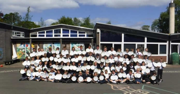 May 2017 - Garstang Soroptimists Forton School children with 133 plates representing a child fed every day in school for a whole year
