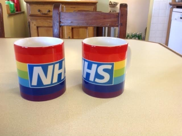 A picture of two coffee mugs with rainbow colours and NHS on side