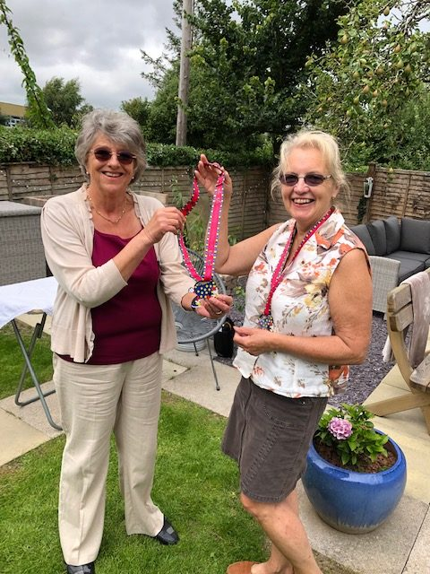 Alex giving out a 10k Virtual Walk medal to Susie at the Tea party we held in Irene`s garden.