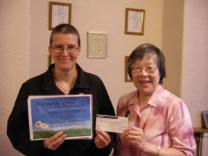 Jane Gregory receives a cheque from Canon Nora Whitham MBE