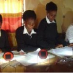 Young girls in Zambia reading with solar lighting