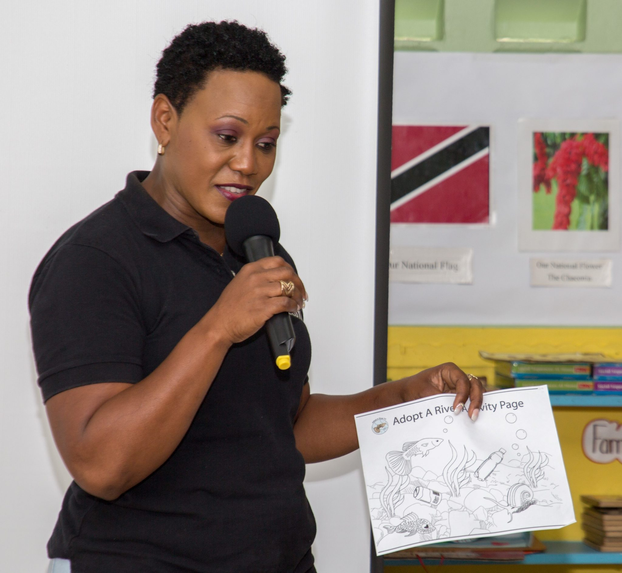 Roslyn George of Cashew Gardens Community Recycling Programme shows the children their activity sheet during her presentation.