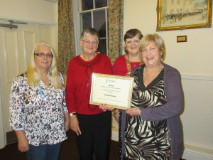 President Sue presents Winner's certificate to volunteers from Cheshire Homes Charity shop