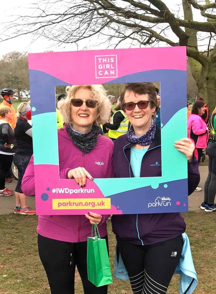 Two Soroptimists in running gear with a cardboard surround of This Girl can for International Women's day 2020