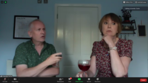 man and woman talking to each other over a glass of wine