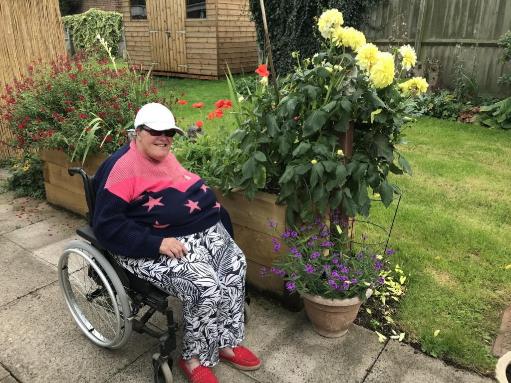 Woman in wheelchair enjoying her raised bed and garden