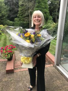 Woman holding a large bouquet of yellow and blue flowers o