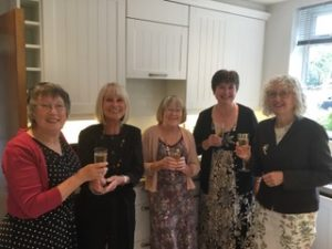 5 women with glasses of wine in a kitchen