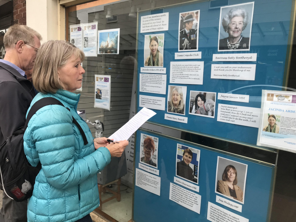 woman in turquoise jacket holding a sheet of paper looking at display in window