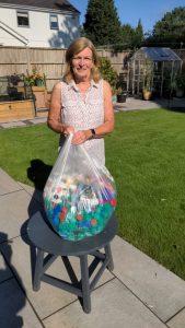 woman in garden with bag of plastic drinks lids