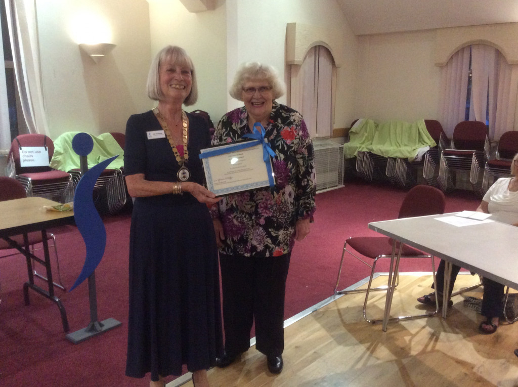 Two women with standing with framed certificate of long service
