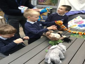 school children playing with the animals in the latest story book