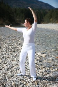 Photo of a woman carrying out Tai Chi exercises against a backdrop of a lake and beach