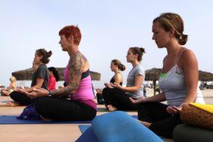 Photo of women attending a yoga class on a beach