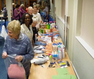 women placing items from a table into clear bags