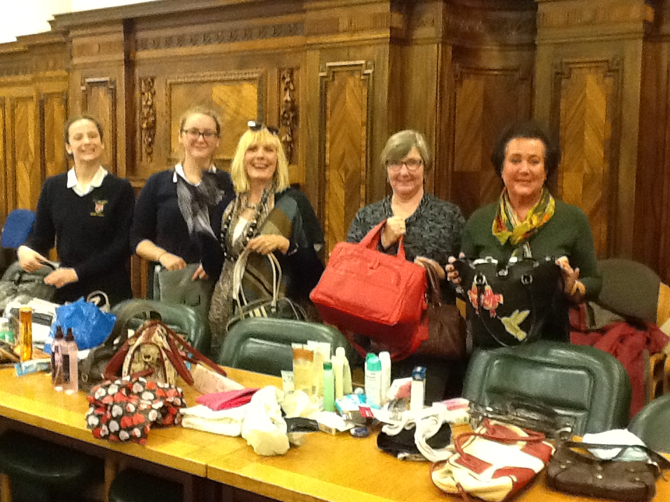 Members filling preloved handbags with girly goodies to give to refugee women.