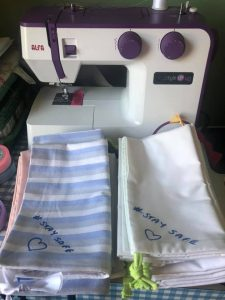 A sewing machine with some finished scrubs bags
