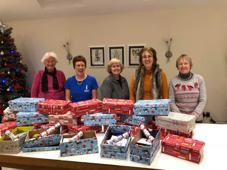 Members of SI Swindon with some of the Christmas gift shoe boxes they pack for the Swindon Nelson Trust Women's Centre. The Club also donated Christmas puddings, mince pies, snacks and biscuits for the Centre's Christmas meal.
