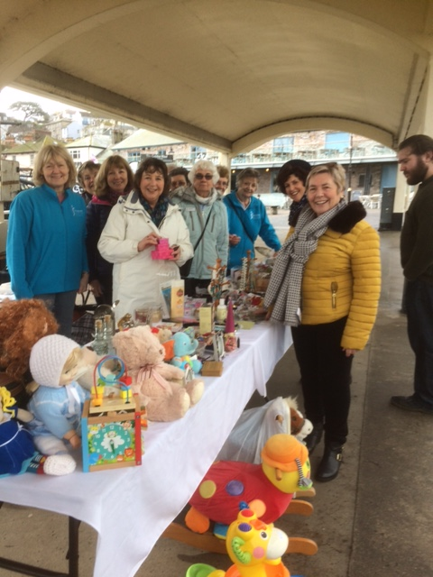 SI Brixham members in the rain and wind selling their wares at the April Fayre on the Quay on Brixham Fish Quay