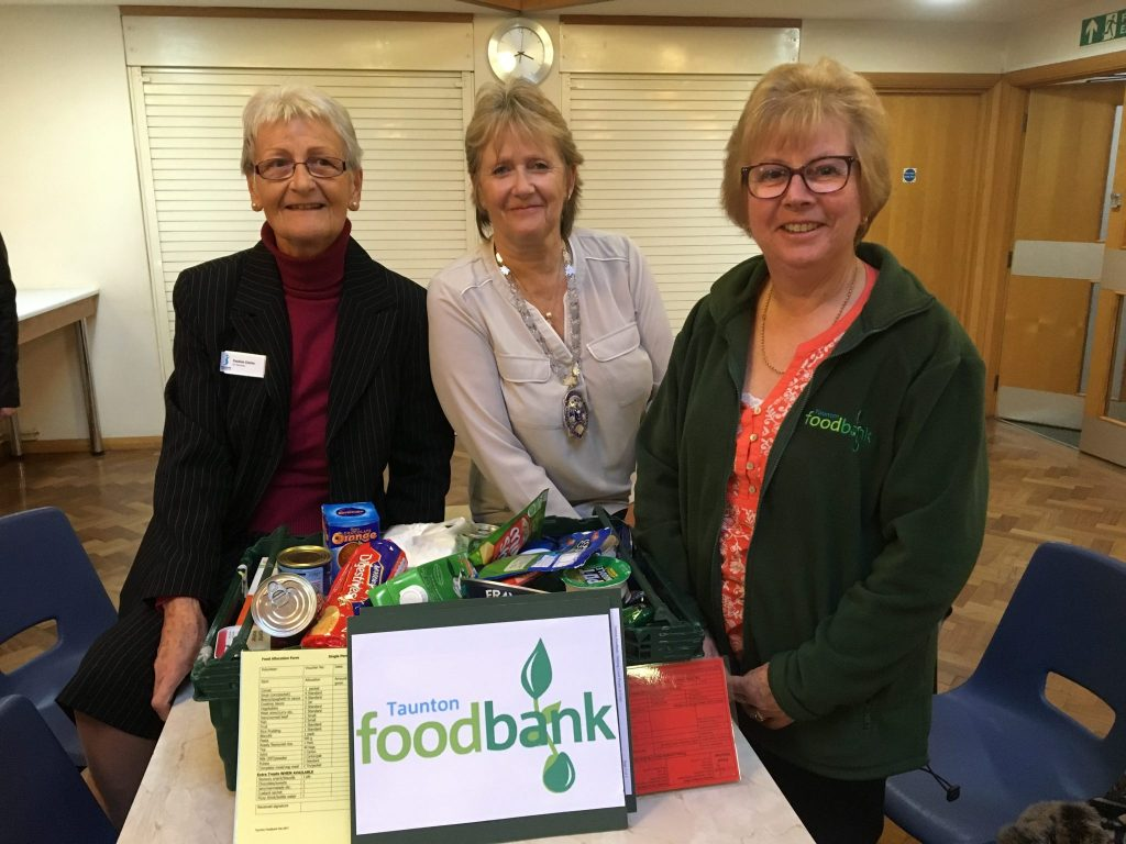 "Members of SI Taunton with a sample box used to support their talk about ""Why the Club supports the Taunton Foodbank"""