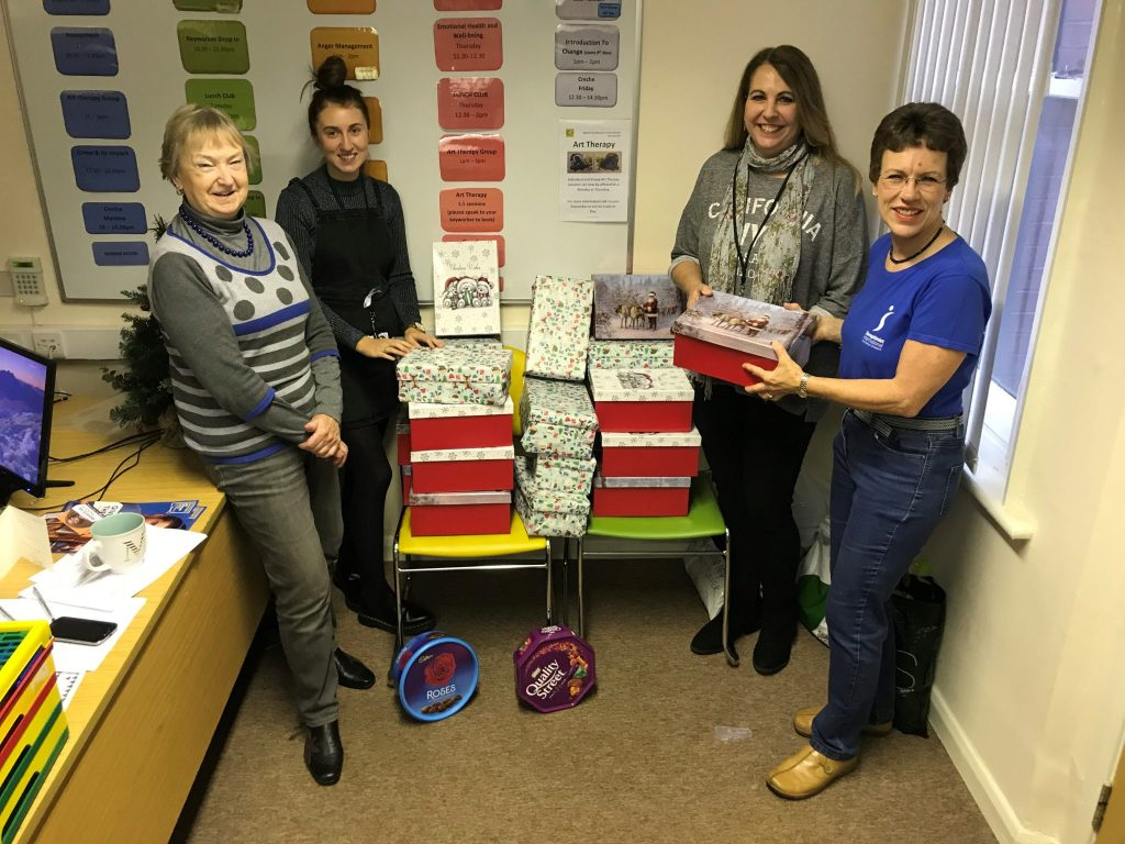 Swindon members Jackie Webb (L) and Lydia Cardew (far R) handing over 25 Christmas shoe boxes to Chessie and Elaine at the Swindon Nelson Trust Women's Centre, for the vulnerable women who use the Centre.