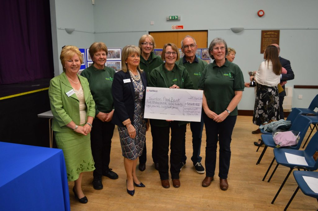 Rhona and Christine from SI Taunton with Sue Weightman, Project Manager at Taunton Foodbank and Foodbank Volunteers, Helen Wallace, Diane Murphy, Alison Perry and Derek Hicks.  The Foodbank will be using the money they received to expand and improve the facilities at the Foodbank Warehouse.