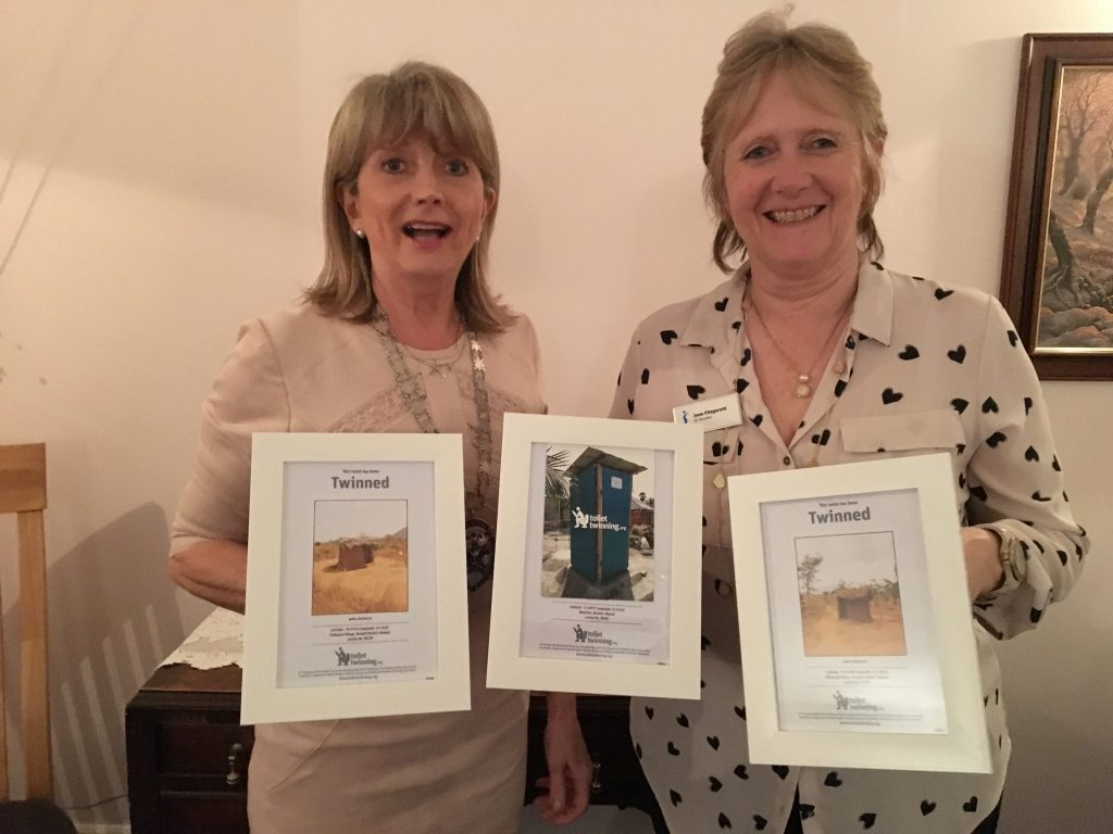 Presidents Rhona and Jane displaying photos of the three toilets we have twinned with - donating money in lieu of sending Christmas cards.