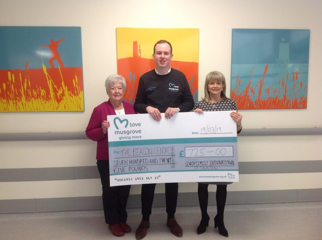 SI Taunton Treasurer and Joint President presenting a cheque to the Beacon Centre at Musgrove Park Hospital.  The £725 was raised at a Quiz Night and £100 was also given to Look Good Feel Better at the Beacon Centre.