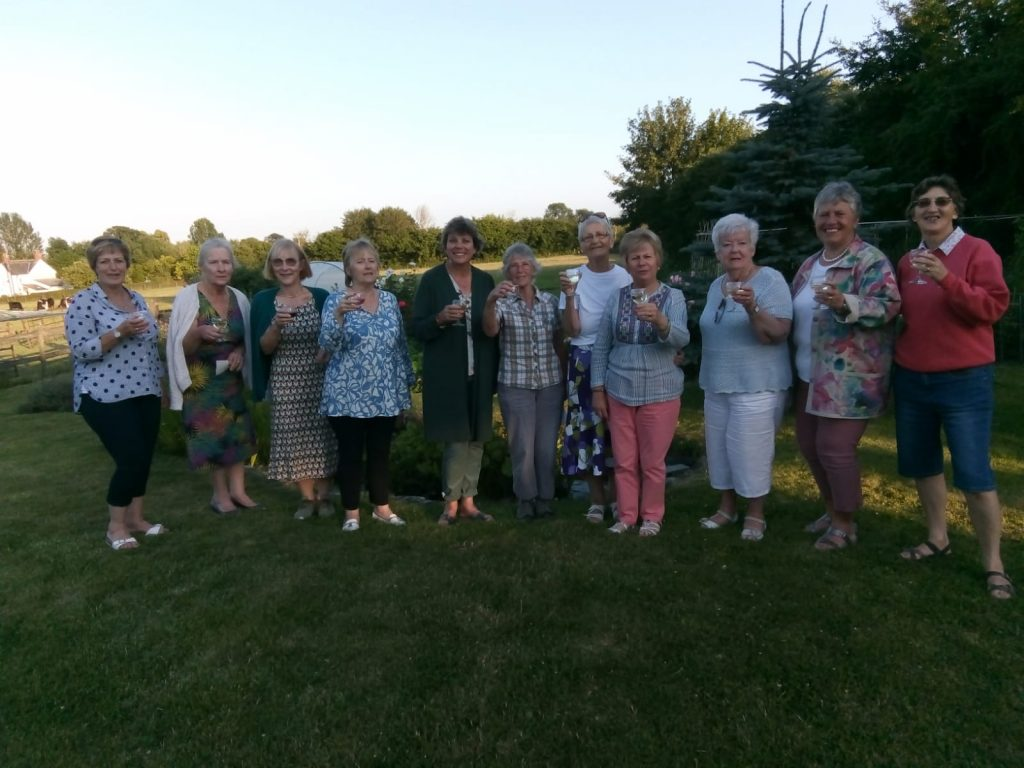 Club members raising a glass at a summer Garden Party which was held to raise funds for the Meru Women's Garden Project.